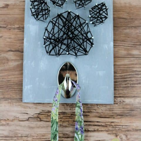 String Art Leash Holder with leash hanging from it.