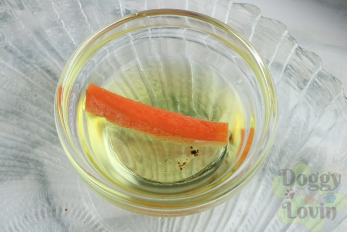 Carrot stick being dipped in oil